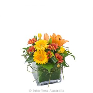 Autumn floral tones in a square glass vase