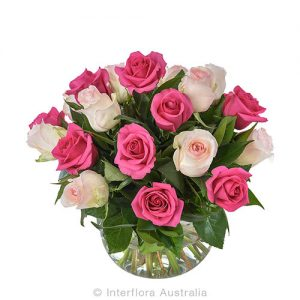 24 mixed roses in a glass squat vase